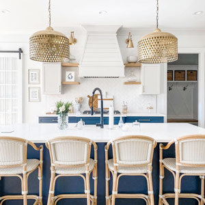 Two cutout gold pendants over a kitchen island