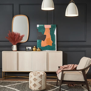 Entry way with two white pendants over a console with abstract art