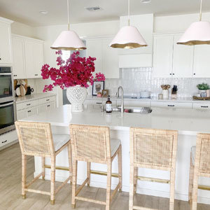 Three pink ruffle pendants hang over a kitchen counter with wicker chairs