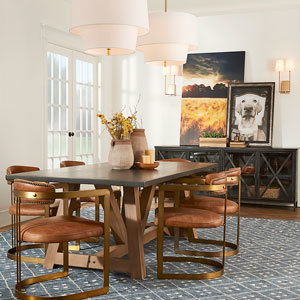 Dining room with art on buffet blue rug and leather chairs