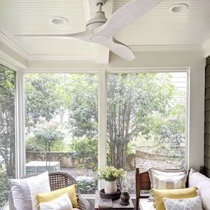 Ceiling fan hanging in a sunroom with couches and pillows