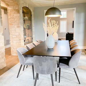 Metal dome chandelier over dining table with neutral chairs and rug