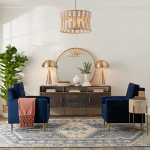A woven drum shade pendant hang between two blue velvet chairs