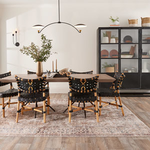 A modern chandelier hangs over a dining room table with woven leather chairs