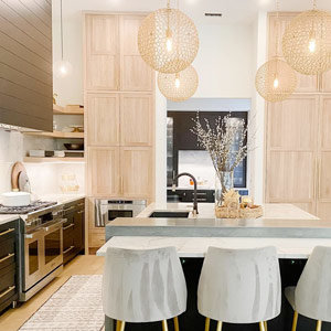 Four globe chandeliers hang over a kitchen island
